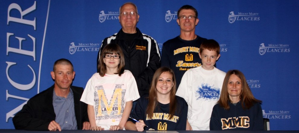 Photo: MMC Head Coaches Hebenstreit (back left) and Fischer with Morgan Hansen (middle front) and her family.